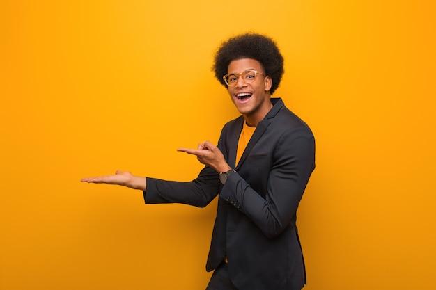 Afroamerikaner des jungen geschäfts über einer orange wand, die etwas mit hand hält