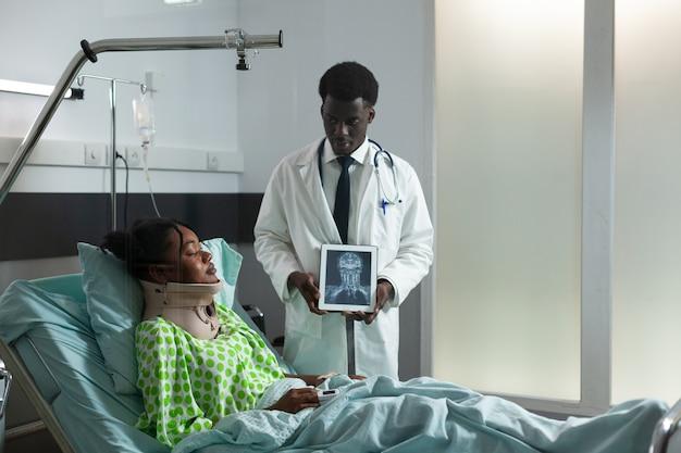 Afroamerikaner, die auf einem digitalen tablet röntgenstrahlen betrachten