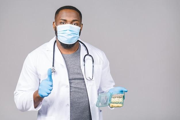 Afroamerikaner-doktor, der pillen zeigt, die handschuhe tragen. doktor hält tabletten. corona-virus-konzept