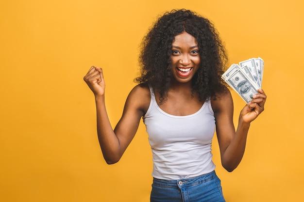 Afroamerikaner erfolgreiche frau 20s mit afro-frisur hält viel geld dollar banknoten