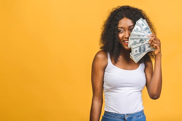 Afroamerikaner erfolgreiche frau mit afro-frisur, die viel geld-dollar-banknoten hält