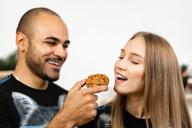 Afroamerikaner füttert seine freundin mit einem keks