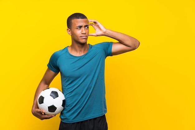 Afroamerikaner-fußballspielermann, der zweifel und mit verwirrtem gesichtsausdruck hat
