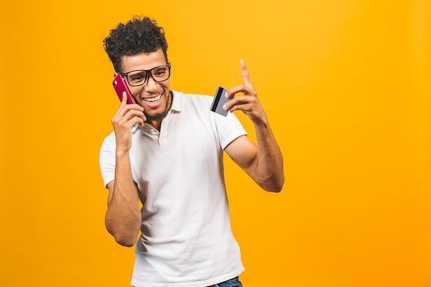 Afroamerikaner gekleidet, unter verwendung des mobiltelefons zeigend plastikkreditkarte.