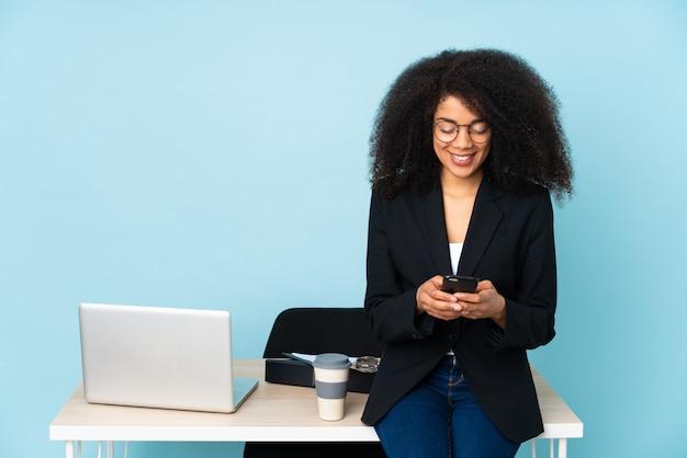 Afroamerikaner-geschäftsfrau, die an ihrem arbeitsplatz arbeitet, der eine nachricht mit dem handy sendet