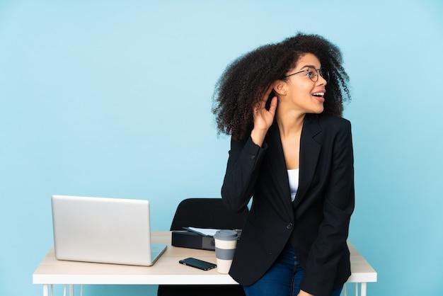 Afroamerikaner-geschäftsfrau, die an ihrem arbeitsplatz arbeitet, der etwas hört, indem man hand auf das ohr legt
