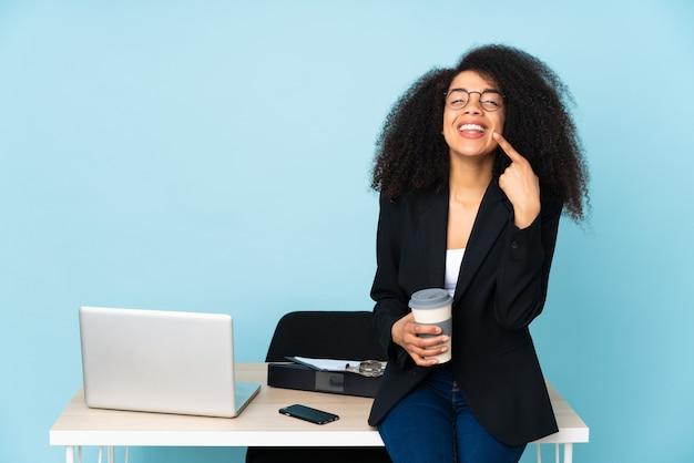 Afroamerikaner-geschäftsfrau, die an ihrem arbeitsplatz arbeitet, der mit einem glücklichen und angenehmen ausdruck lächelt