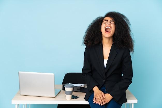 Afroamerikaner-geschäftsfrau, die an ihrem arbeitsplatz arbeitet, der mit offenem mund nach vorne schreit