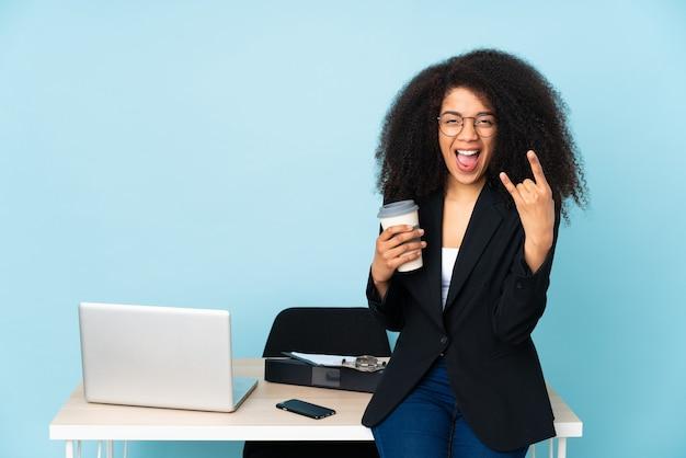Afroamerikaner-geschäftsfrau, die an ihrem arbeitsplatz arbeitet, der rockgeste macht