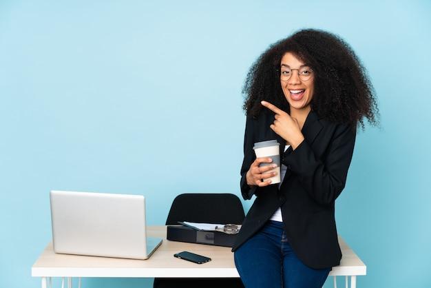 Afroamerikaner-geschäftsfrau, die an ihrem arbeitsplatz arbeitet, überrascht und zeigt seite