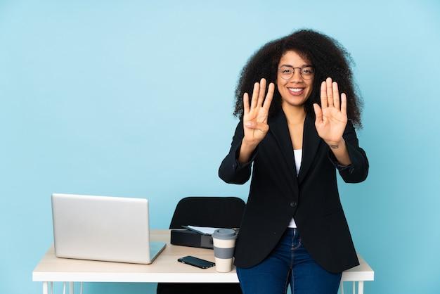 Afroamerikaner-geschäftsfrau, die an ihrem arbeitsplatz arbeitet und neun mit den fingern zählt