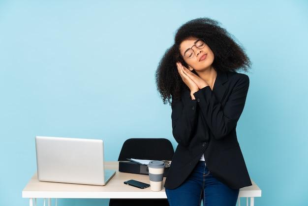Afroamerikaner-geschäftsfrau, die an ihrem arbeitsplatz arbeitet und schlafgeste in entzückendem ausdruck macht