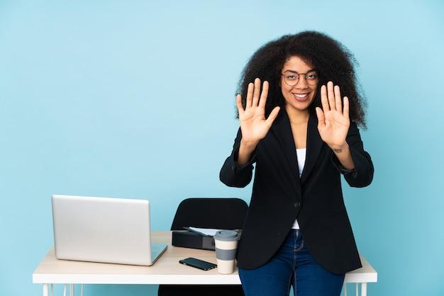 Afroamerikaner-geschäftsfrau, die an ihrem arbeitsplatz arbeitet und zehn mit den fingern zählt