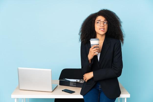 Afroamerikaner-geschäftsfrau, die an ihrem arbeitsplatz mit verwirrendem gesichtsausdruck arbeitet