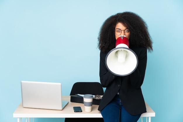 Afroamerikaner-geschäftsfrau, die in ihrem arbeitsplatz arbeitet, der durch ein megaphon schreit