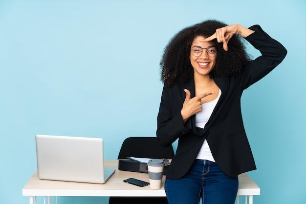Afroamerikaner-geschäftsfrau, die in ihrem arbeitsplatz fokussierendes gesicht arbeitet. rahmensymbol