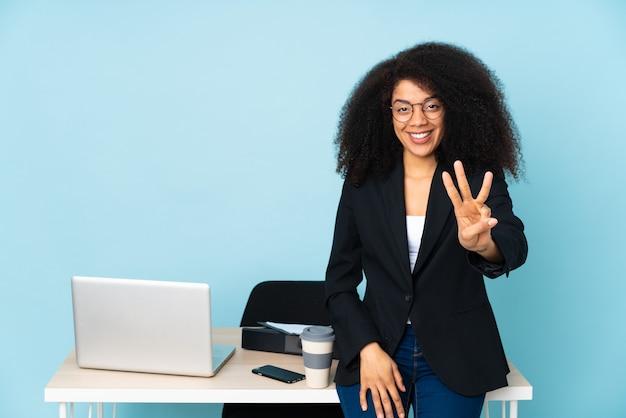 Afroamerikaner-geschäftsfrau, die in ihrem arbeitsplatz glücklich arbeitet und drei mit den fingern zählt
