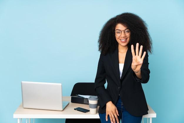 Afroamerikaner-geschäftsfrau, die in ihrem arbeitsplatz glücklich arbeitet und vier mit den fingern zählt