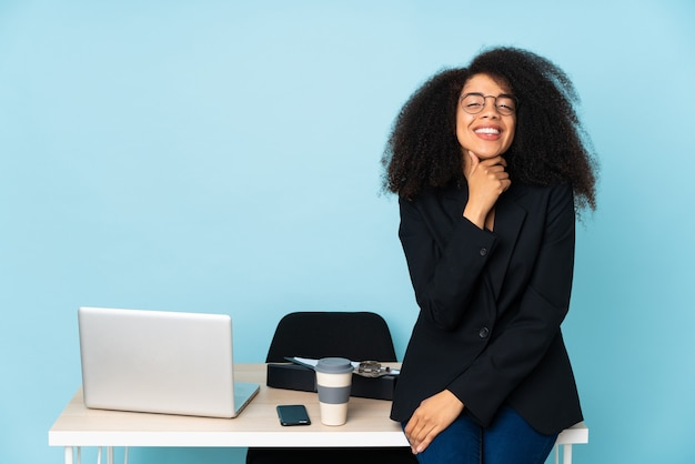 Afroamerikaner-geschäftsfrau, die in ihrem arbeitsplatz mit brille arbeitet und lächelt