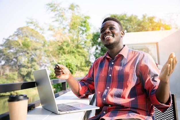 Afroamerikaner gutaussehender mann, der laptop für geschäft verwendet und geld online oder manuell überträgt. erfolgsökonomisches konzept.