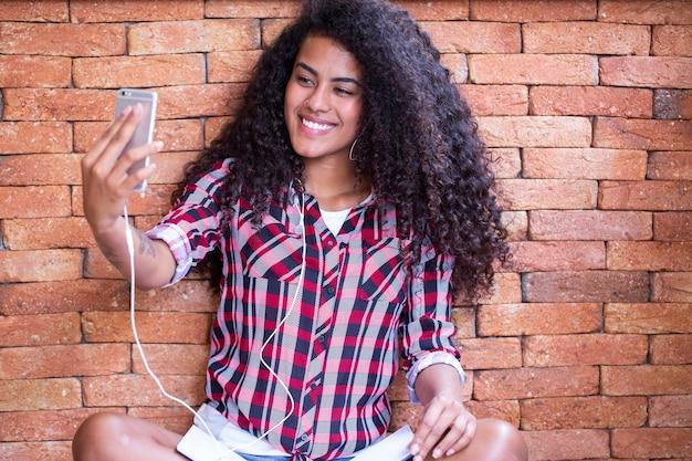 Afroamerikaner junge studentin, die selfie-foto auf frontkamera des smartphones für das teilen in netzwerken macht, die im boden sitzen