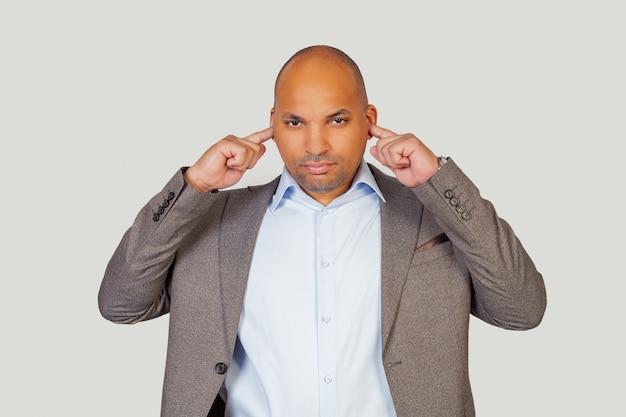 Afroamerikaner junger mann kerl mit wütendem ausdruck, der seine ohren mit seinen fingern für lautes musikgeräusch bedeckt