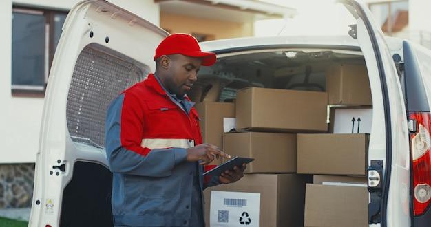 Afroamerikaner junger postbote im roten kostüm und in der kappe, die die briefkästen in einem van mit tablet-gerät in händen zählen. draußen.