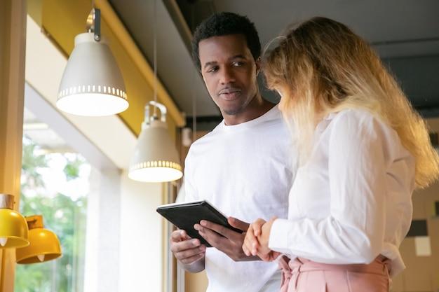 Afroamerikaner kerl, der blonden klienten betrachtet und tablette hält
