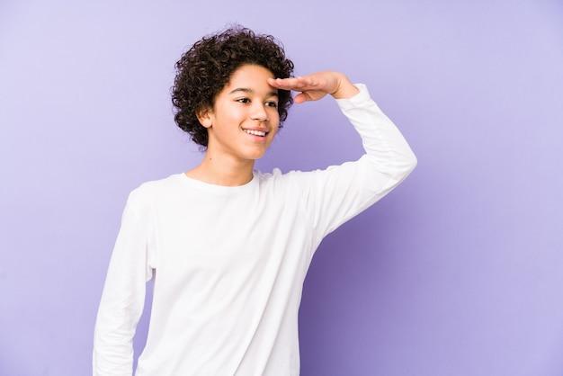 Afroamerikaner kleiner junge isoliert, der weit weg schaut und hand auf stirn hält.