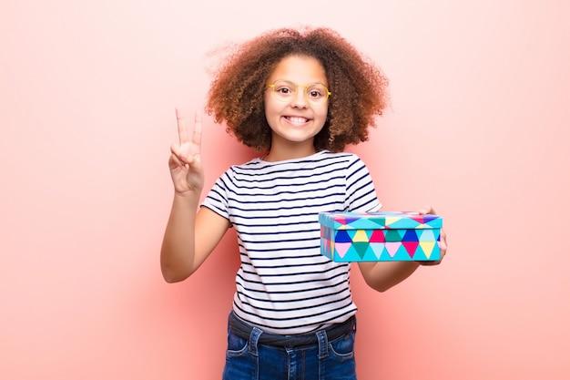 Afroamerikaner kleines mädchen, das eine geschenkbox hält