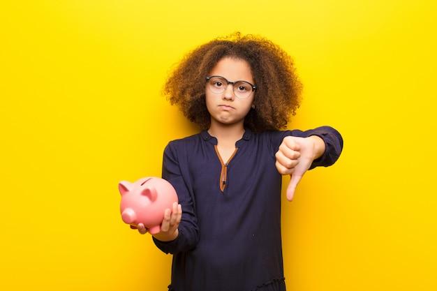 Afroamerikaner kleines mädchen gegen flache wand, die ein sparschwein hält