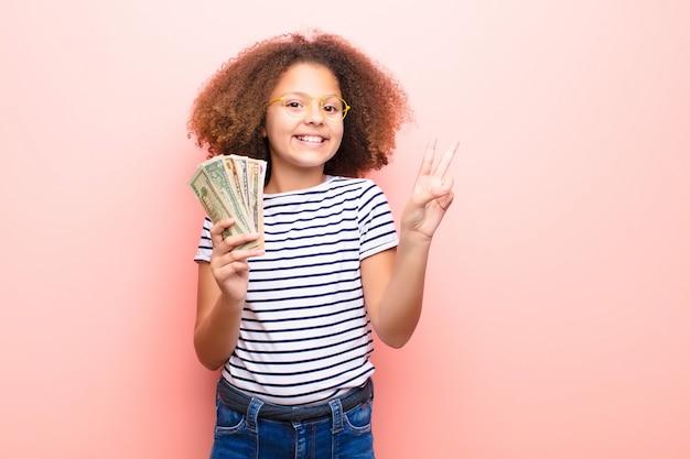 Afroamerikaner kleines mädchen gegen flache wand mit dollar-banknoten