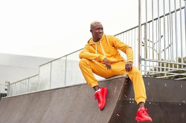 Afroamerikaner lächelnder schwarzer mann gelber kapuzenpulli draußen glücklicher emotionaler afro-modellmann, der skatepark-sommertag sitzt freier raum