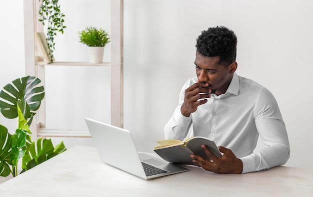 Afroamerikaner mann, der das handbuch liest