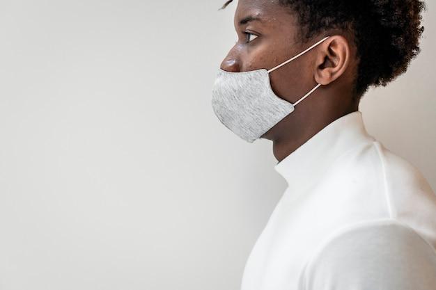 Afroamerikaner mann, der eine gesichtsmaske in der neuen normalität trägt
