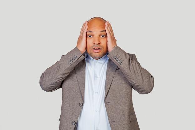 Afroamerikaner mann, der hände auf kopf mit glücklicher aufregung hält, kann gute nachrichten nicht glauben