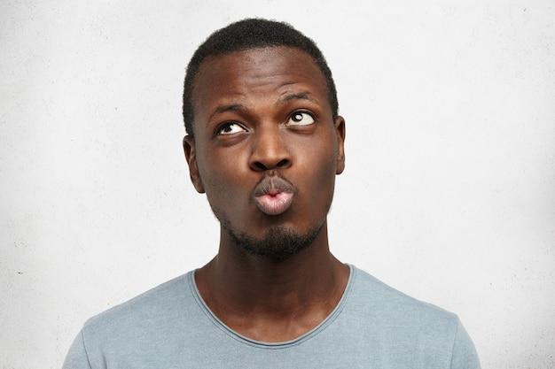 Afroamerikaner-mann, der lässiges graues hemd trägt, schmollende lippen trägt und mit unentschlossenem ausdruck aufblickt