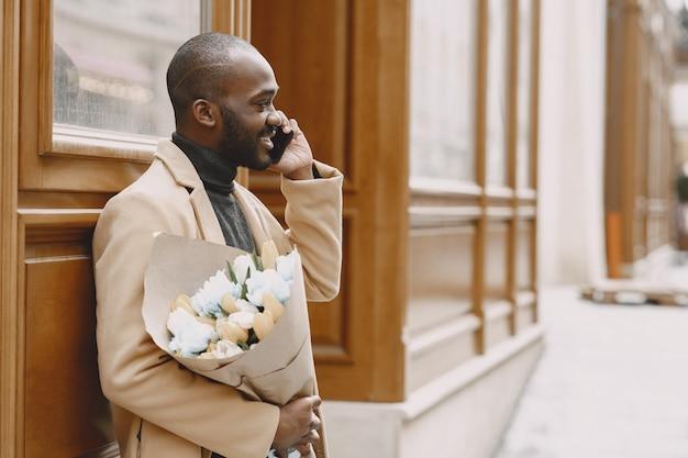 Afroamerikaner mann in einer stadt. kerl, der blumenstrauß hält. männchen in einem braunen mantel.