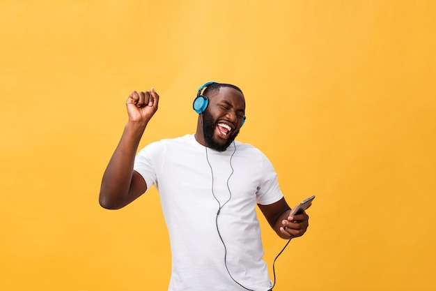 Afroamerikaner mann mit kopfhörern hören und tanzen mit musik.