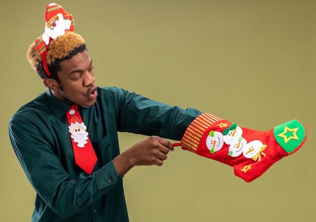 Afroamerikaner-mann mit lustigem weihnachtsmannrand und roter krawatte, die weihnachtsstrumpf hält, der sie betrachtete, überraschte das stehen über grüner wand