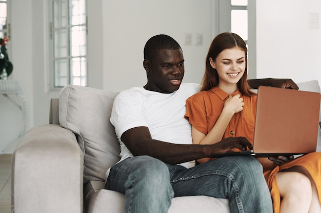 Afroamerikaner mann und weiße frau arbeiten zu hause freiberuflich laptop, paar