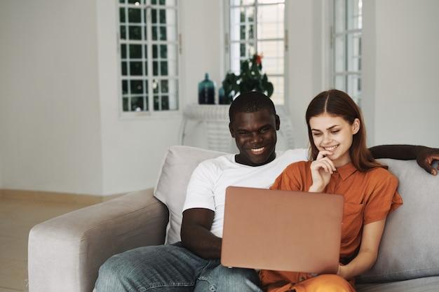 Afroamerikaner-mann und weiße frau, die den laptop im sofa verwenden und zu hause entspannen