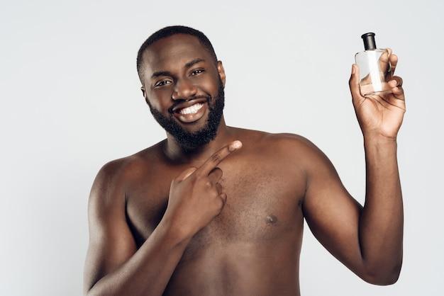 Afroamerikaner mann verwendet aftershave lotion. männerhygiene.