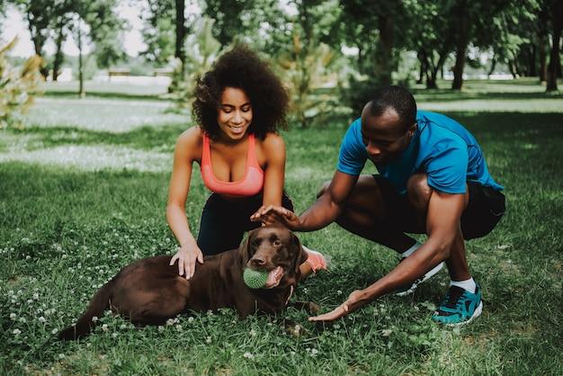 Afroamerikaner-paare in der sportkleidung, die hund streichelt.