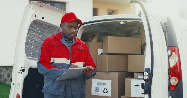 Afroamerikaner-postbote in der roten uniform und in der kappe, die am weißen van mit kartonschachteln stehen und dokumente in der zwischenablage ausfüllen. draussen.