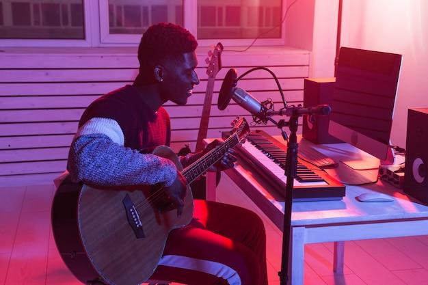 Afroamerikaner professioneller musiker, der gitarre im digitalen studio zu hause aufnimmt, musikproduktion