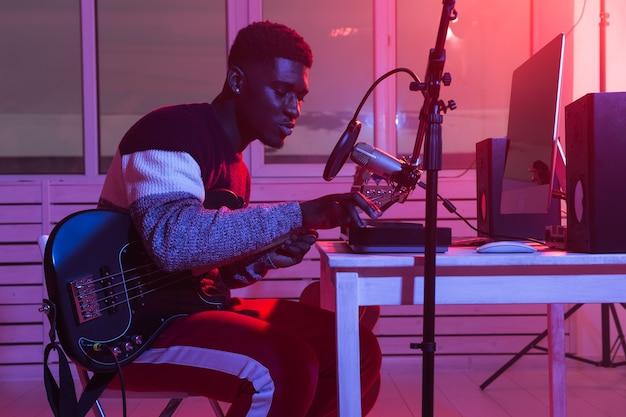 Afroamerikaner professioneller musiker, der synthesizer im digitalen studio zu hause aufnimmt, musik