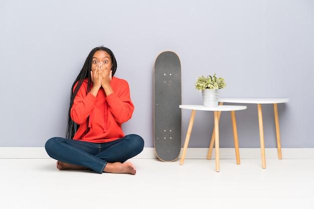 Afroamerikaner-schlittschuhläufer-jugendlichmädchen mit dem umsponnenen haar, das auf dem boden mit überraschungsgesichtsausdruck sitzt