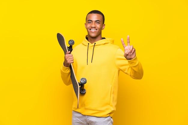 Afroamerikaner-schlittschuhläufermann, der siegeszeichen lächelt und zeigt