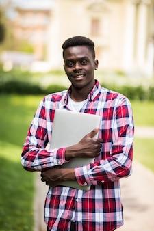 Afroamerikaner-student mit laptop im sonnigen tag auf der stadtstraße